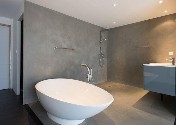 enduit béton ciré pour murs de salle de bain ouverte avec douche italienne et baignoire ilot