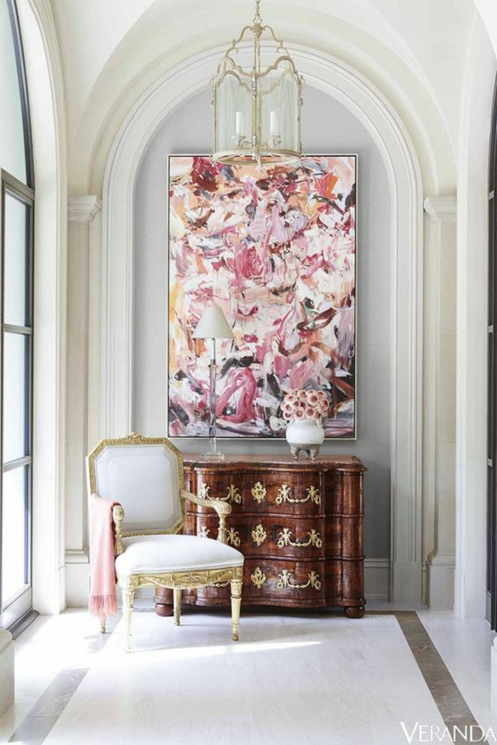 chambre rose poudré et taupe, grand tableau rectangulaire en style art abstrait, luminaire en verre et en métal doré, carrelage blanc aux effets marbrés, fauteuil en tissu blanc et en style baroque
