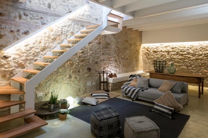 salon moderne avec objets traditionnels, déco avec canapé gris et tapis noir couverts de poufs et de coussins