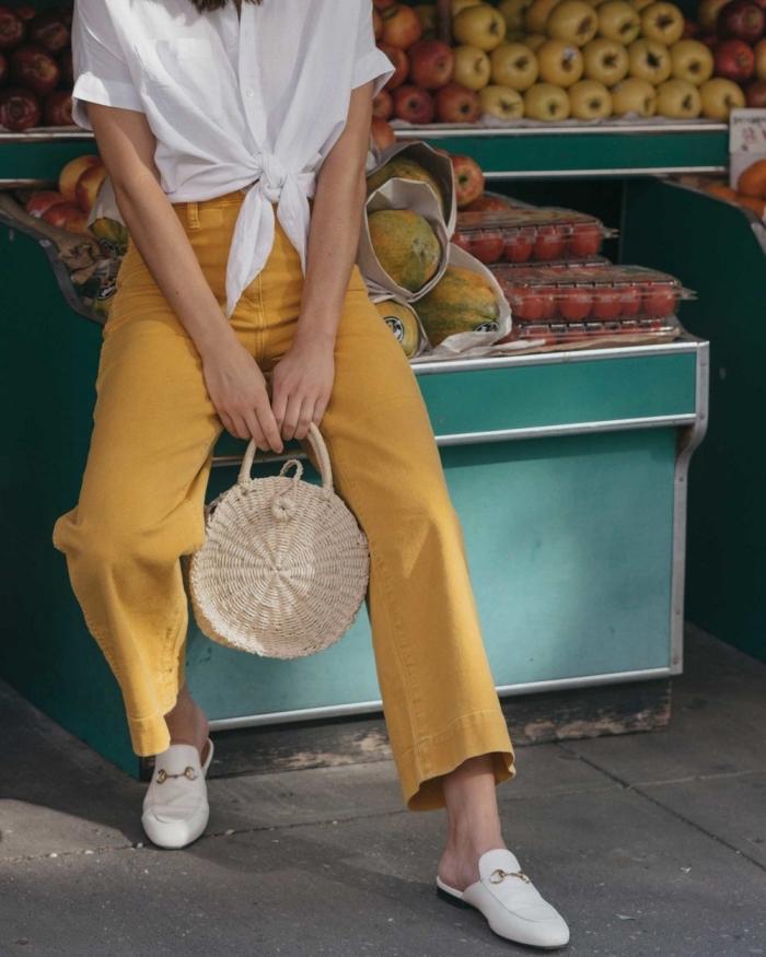 modèle de pantalon large à taille haute avec chemise blanche nouée et sac à main de style balinais beige