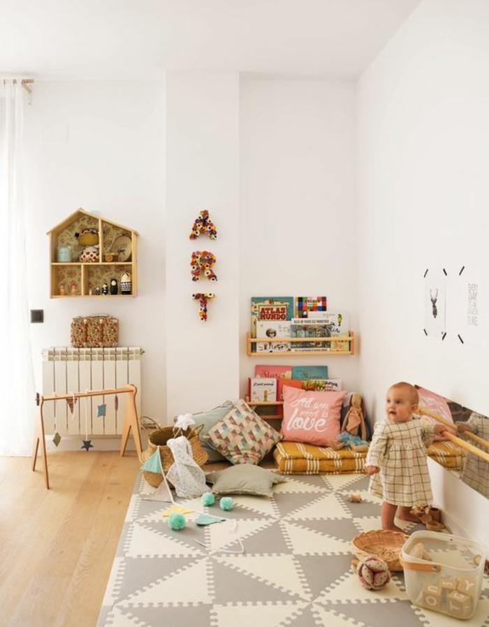 lit bébé sans barreau, avec couverture en gris perle et blanc aux losanges, murs et plafond blancs, étagère rangement en forme de maison en bois clair, fillette avec robe a carreaux blancs et marron
