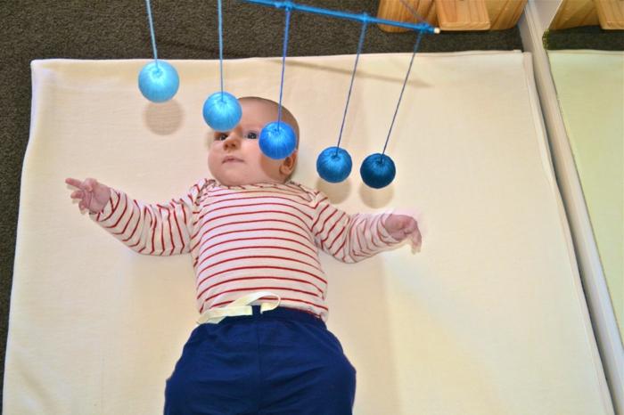lit cabane montessori, chambre montessori, bébé qui joue avec cinq boules en bleu roi, lit montessori, lit sans barreau