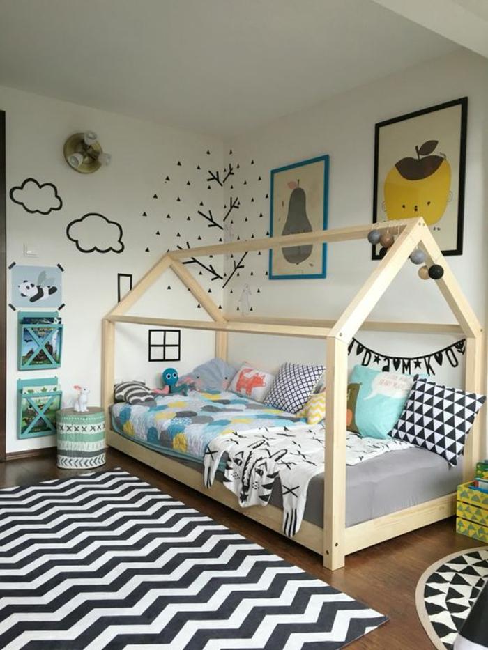 lit bébé sans barreau, chambre montessori, grand tapis en noir et blanc avec des motifs graphiques, dessins en noir sur le mur blanc, nuages, arbre et fenêtre et cheminée de maison
