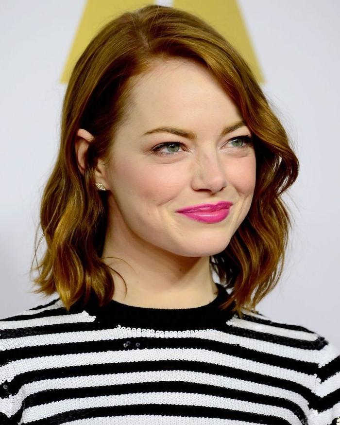 emma stone avec une coiffure carré mi long avec des boucles sur cheveux roux, top à rayures noir et blanc