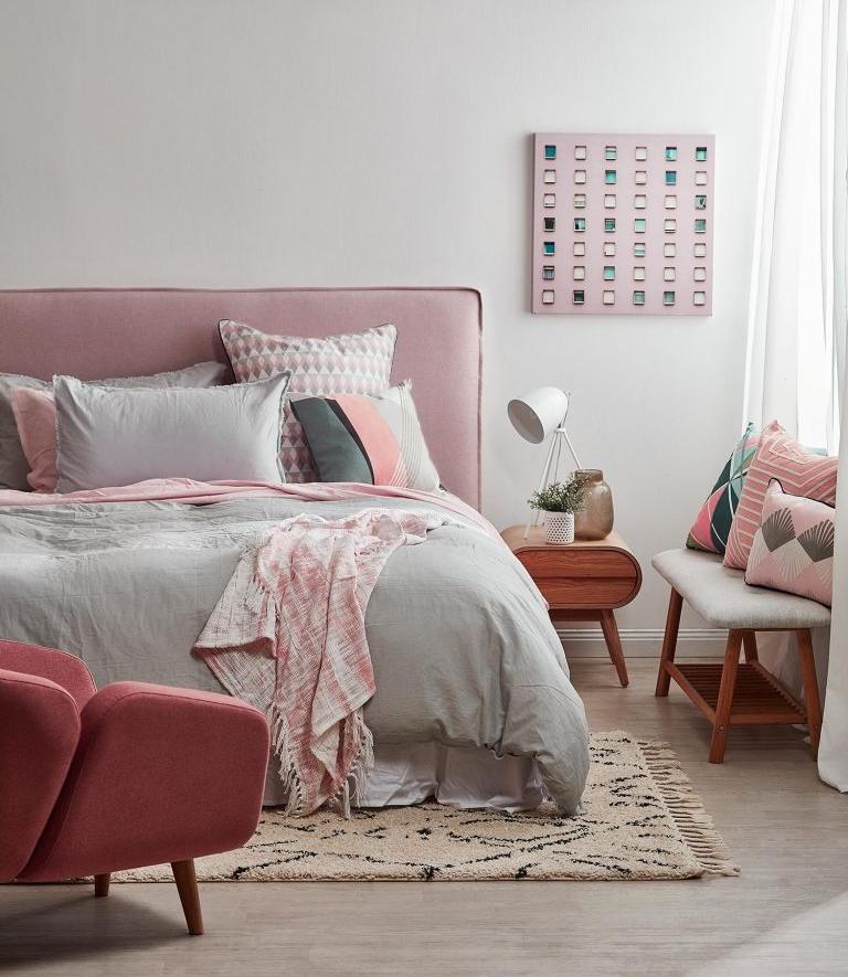 chambre rose poudré et taupe, avec du gris, murs gris, petit panneau rose avec des petits carrés décoratifs multicolores, parquet en PVC, fauteuil en rose poudré, tapis aux franges en beige avec des losanges noirs, tabouret avec tissu gris et pieds en bois marron