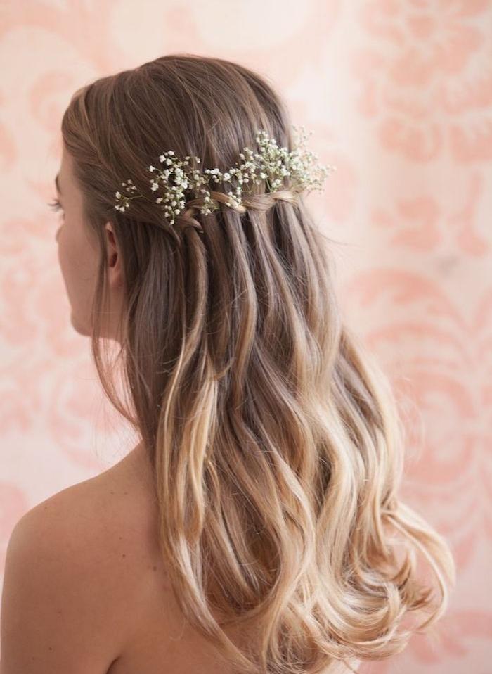 exemple de tresse en cascade femme, avec une décoration de fleurs fraîches blanches, cheveux ondulés