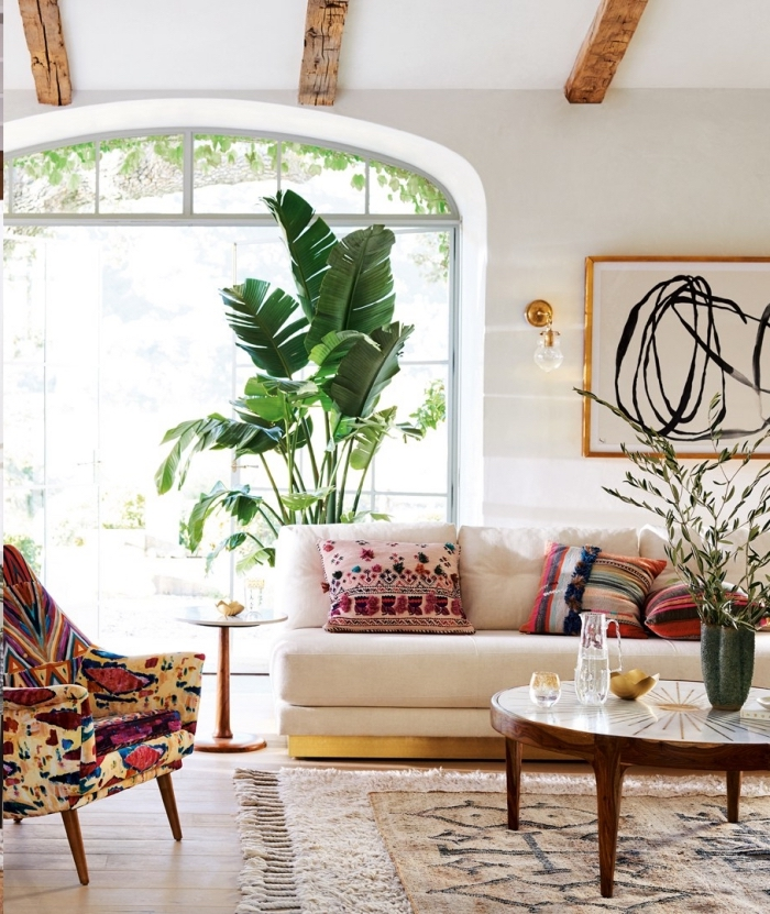 salon blanc aménagé en style chic ethnique avec plantes vertes exotiques et coussins multicolore aux motifs tribaux