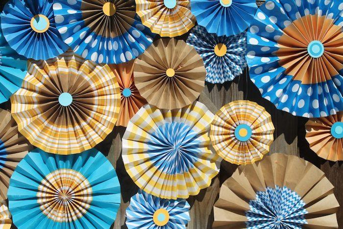 fabriquer éventail soi meme en papier marron, jaune et bleu, decoration mur originale pour une fete