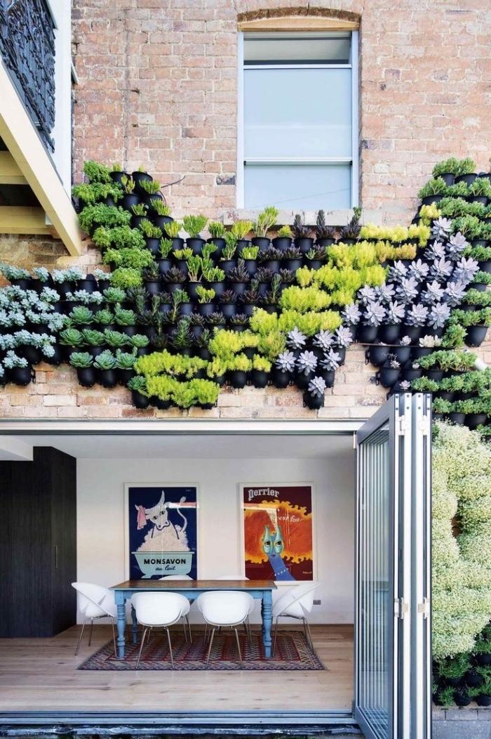 une façade végétalisée composée d'une multitude de pots fixé au mur, en-dessus de la porte de la véranda