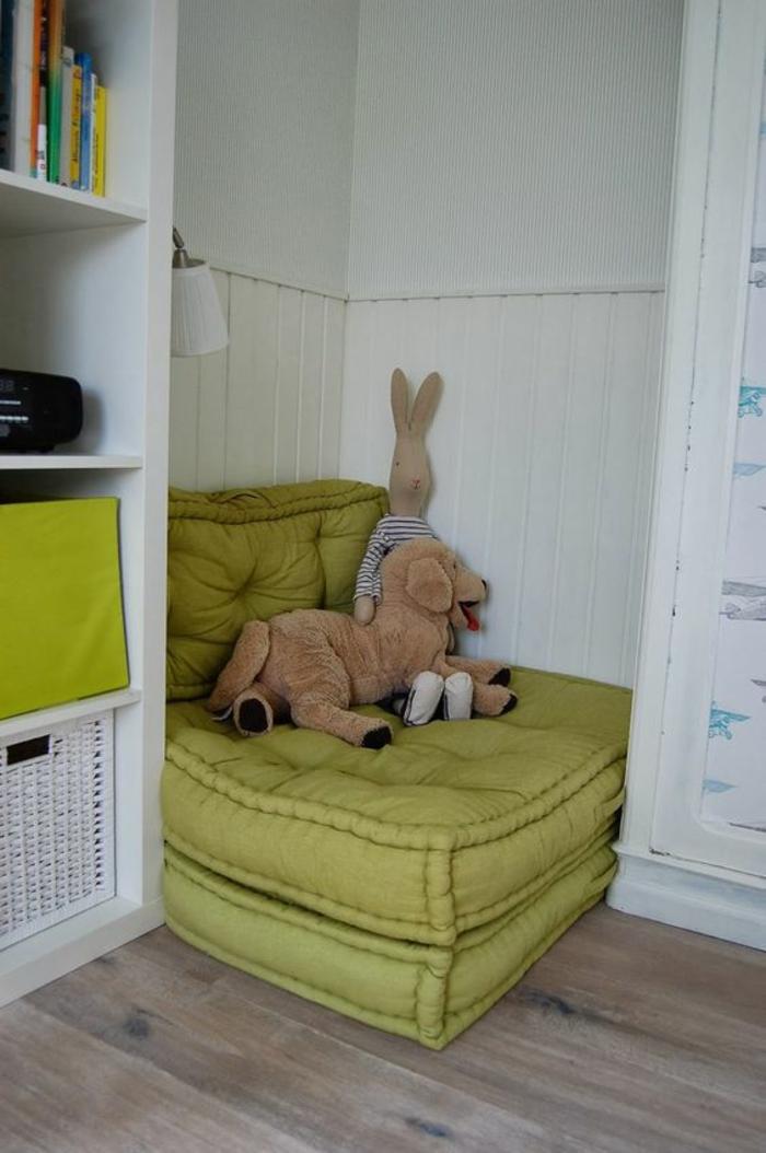 chambre montessori, meuble montessori, fauteuil en vert réséda dans un angle entre deux meubles de rangement, armoire et bibliothèque