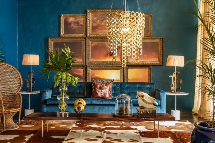 idée pour une deco ethnique aux murs en bleu canard et mur de cadres dorés, modèles de fauteuil paon en rotin