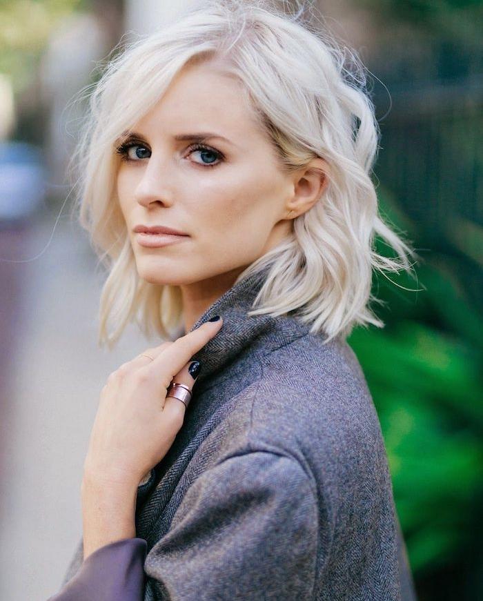 coloration blond polaire sur cheveux coupés en carré, boucles légères, manteau femme gris