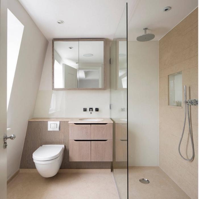 modèle de salle de bain mansardée au plafond blanc avec cabine de douche en carrelage beige et meuble fonctionnel beige