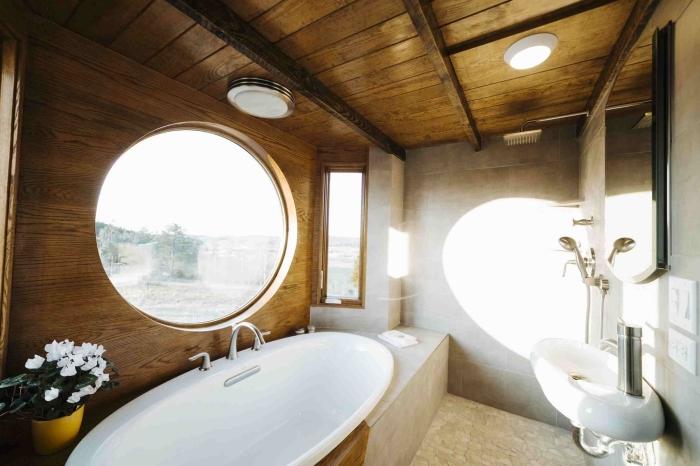 modèle de salle de bain mansardée équipée d'une baignoire ovale au plafond de bois foncé et revêtement en carrelage gris clair