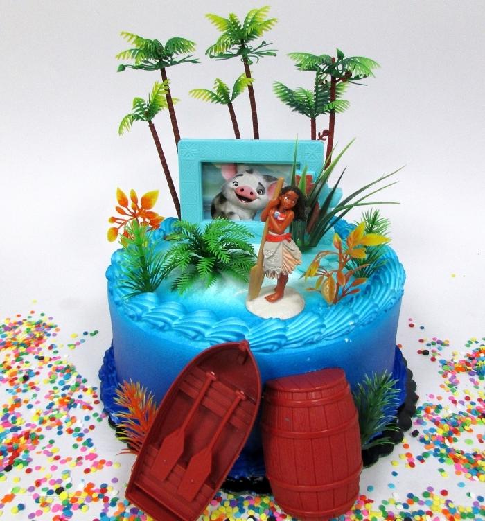 idée pour une deco vaiana avec un gâteau fait maison au glaçage turquoise et figurines Vaiana et bateaux