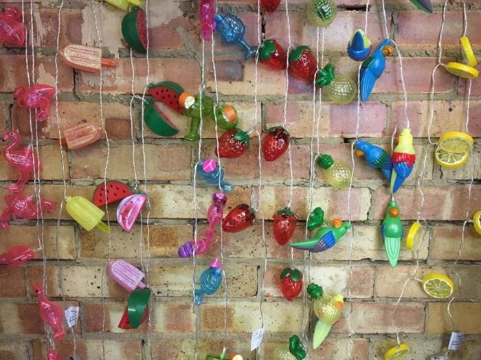mur en briques oranges et marron, effet usé, une dizaine de guirlandes aux motifs rondelles de citron jaune, perroquets, déco flamant rose, fraises, glaces, sorbets et ananas, guirlande lumineuse pour chambre ou jardin