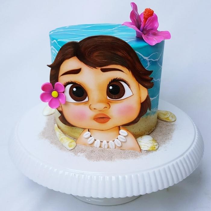 ideé deco vaiana sur un gâteau Disney réalisée avec fondant turquoise et blanc, modeler le visage bébé vaiana en fondant et colorants alimentaires