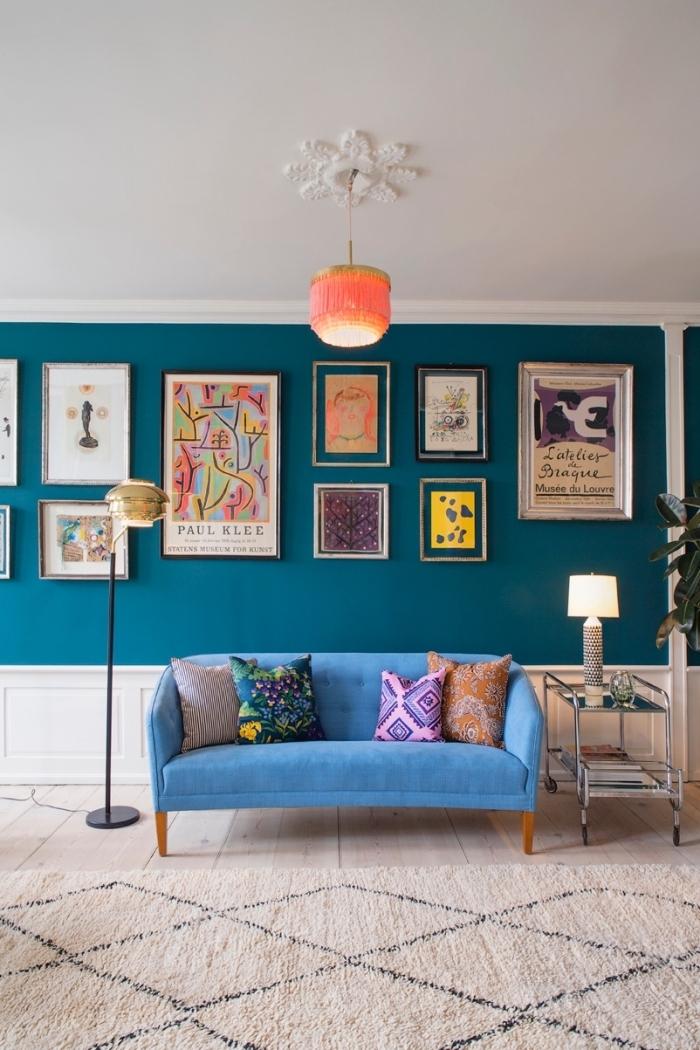 mur bleu canard sublimé par une galerie photos aux tons gais et un canapé d'une nuance de bleu turquoise