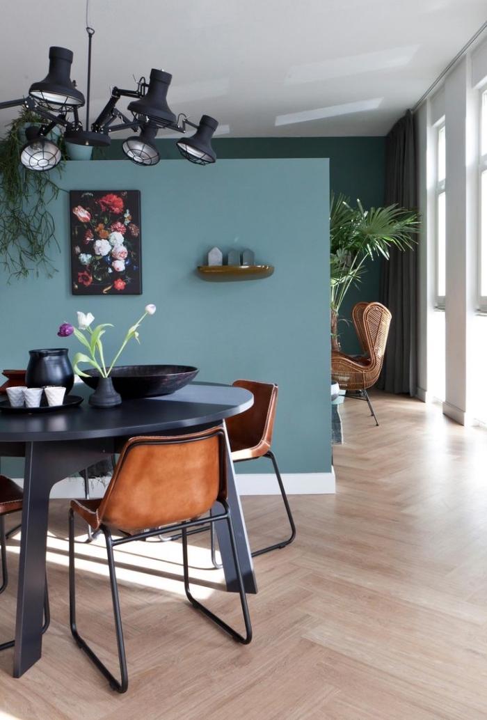 utilisation de différentes tonalités de la peinture bleu pétrole permet de séparer visuellement les deux espaces distincts du salon et de la salle à manger