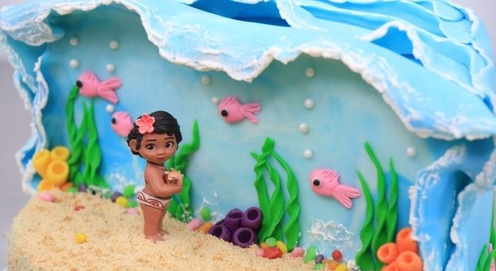 magnifique exemple de gâteau fait maison sur le thème Disney, modèle gâteau à design océan et sable avec figurine bébé vaiana