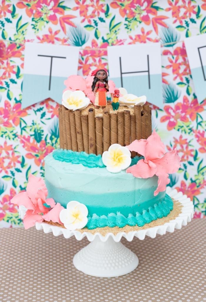 jolie idée de deco vaiana sur un gâteau à deux étages à design océan et sable avec figurines Vaiana et Hei hei