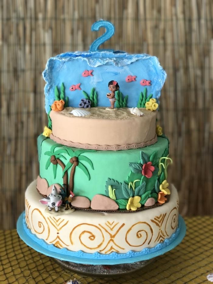 exemple de magnifique gâteau fait maison sur le thème Vaiana à trois étages avec étage sable et nature en fondants colorés