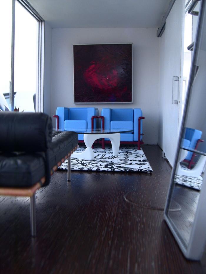sol en bois wengé, grand fauteuil en cuir, fauteuils bleus, table basse ovale, grand miroir rectangulaire