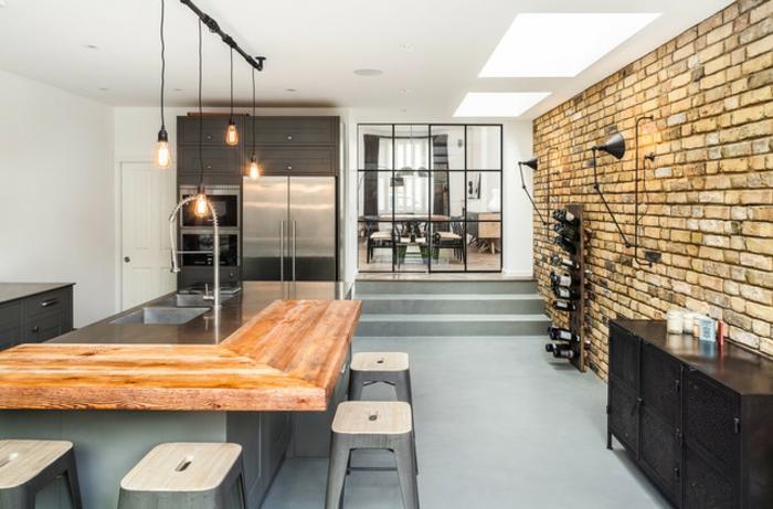 appartement industriel, bar en L avec tabourets industriels, lampes ampoules, mur en briques, verrier industrielle cuisine