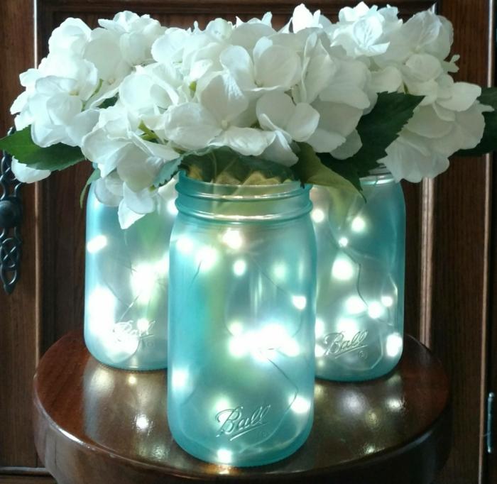 trois pots en verre mat avec des fleurs magnolias blanches artificielles, guirlande lumineuse led dans les pots, table de chevet ronde en bois marron