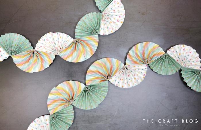 comment faire une guirlande en éventails de papier à motifs divers pour décorer un mur gris