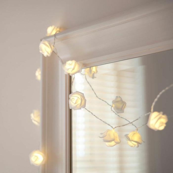roses en verre mat blanc, accrochées sur le cadre blanc d'un grand miroir, guirlande lumineuse boule, guirlande lumineuse interieur