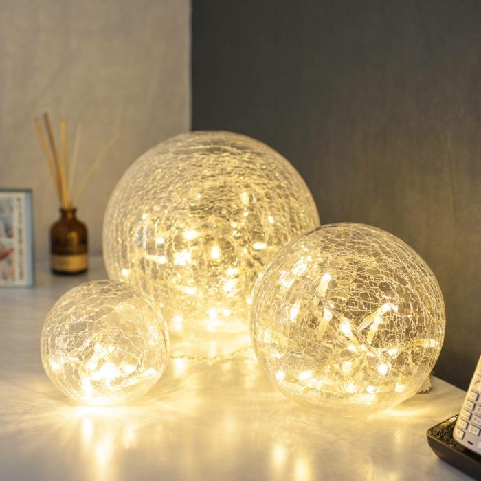 guirlande lumineuse ampoule, guirlande a pile, chambre adulte cocooning, trois boules de taille diverse sur une table de chevet avec des guirlandes dans leur interieur