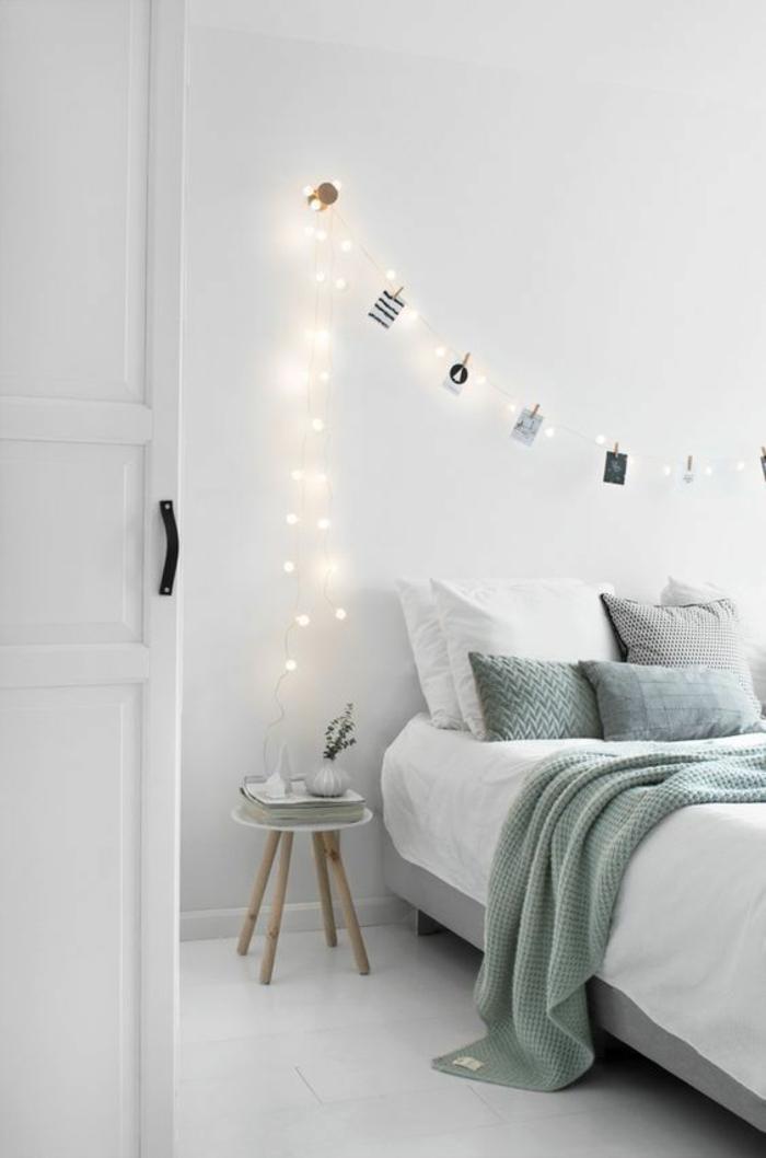 chambre en style scandinave, murs blancs, porte blanche, carrelage blanc, petit tabouret rond a quatre pieds en bois clair, utilisé comme table de chevet, guirlande lumineuse interieur, pinces lumineuses pour suspendre les photographies