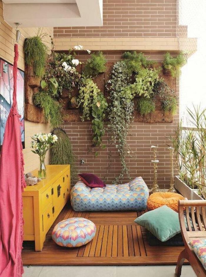 idée originale pour l'aménagement d'un mur végétalisé en fibre de coco, déco de balcon bohème chic avec des poufs et des coussins colorés