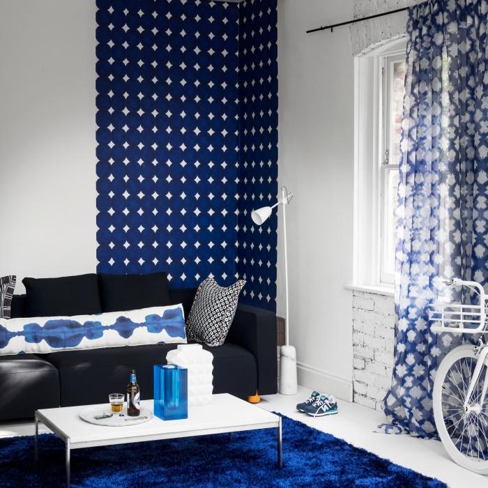 la déco aux imprimés bleus qui rappellent latechnique tie and dye crée un joli contraste avec le blanc des murs, un canapé bleu marine sublimé par les coussins tie and dye et le lé de papier peint imprimé