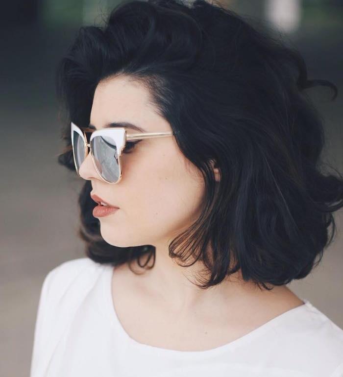 coupe au carré flou avec des boucles naturelles et une mèche rejeté sur le côté, cheveux noirs volumineux, lunette de soleil retro chic