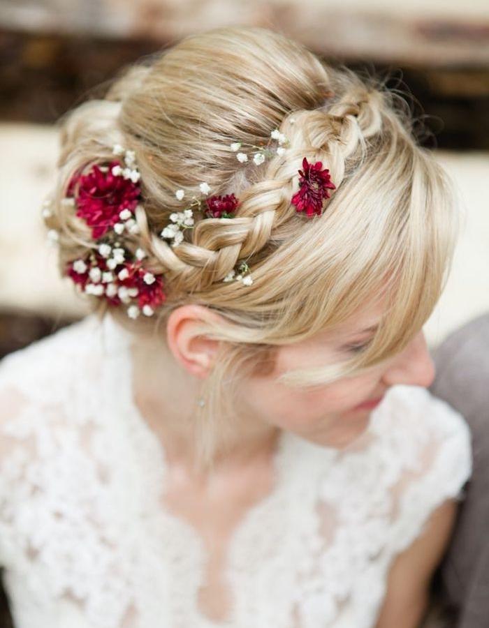 coiffure de mariée avec une tresse en couronne, mèches libres de devant et décoration de fleurs rouges et blanches