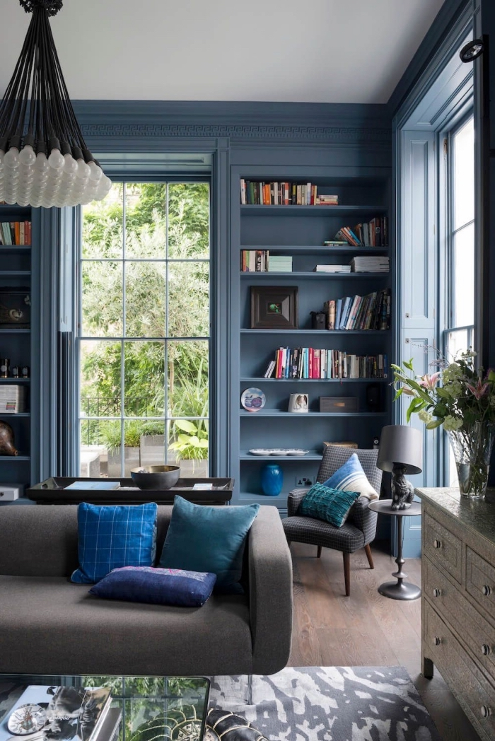 salon bleu et gris avec mur bibliothèque et encadrement peints en bleu marine pour structurer l'espace et lui donner de la profondeur