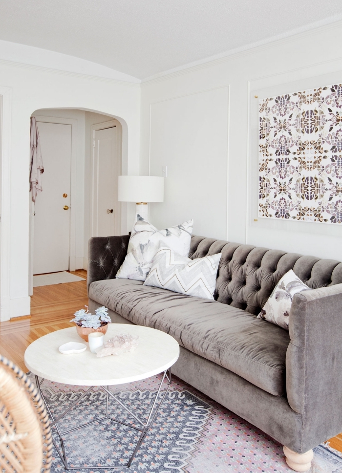 tapisserie moderne de papier peint imitation carreaux de ciment encadré façon tableau d'art qui fait écho aux couleurs du canapé et du tapis