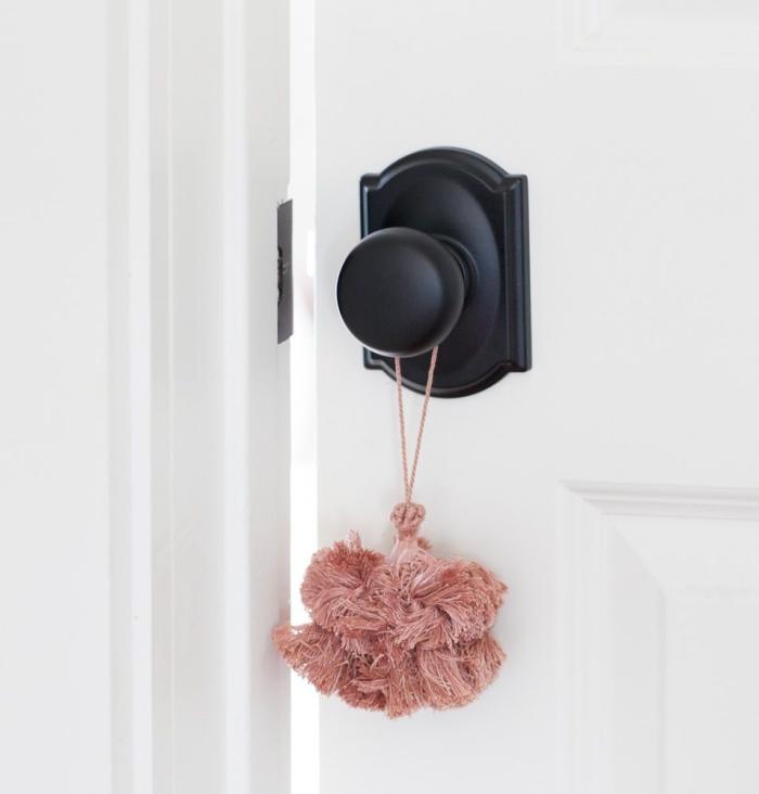 une jolie manière de mettre en valeur un bouton meuble noir, pompon déco de porte rose pour un joli accents bohème chic