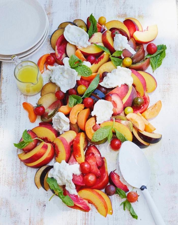 une salade de fruits maison à l'italienne bien gourmande, de pêches, cerises et prunes, avec des morceaux de burrata et vinaigrette maison