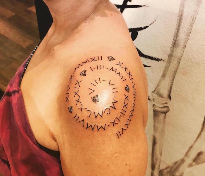 tattoo femme sur épaule spirale avec dates en chiffres romains et diamants