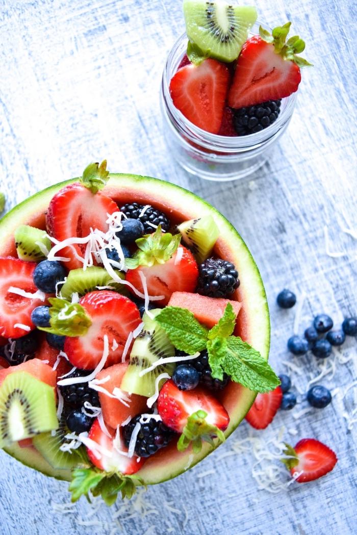 une salade de fruits originale, de fraises, kiwi, myrtilles, mûres et noix de coco, dressée dans un bol de demie-pastèque