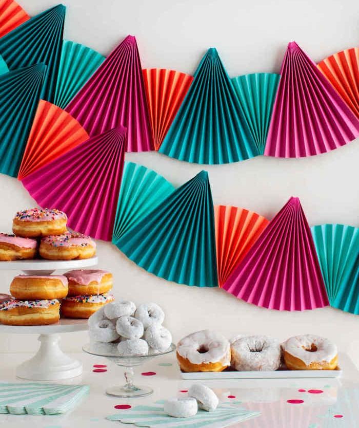deco anniversaire a faire soi meme en éventails colorés sur un mur blanc derrière un candy bar en donuts