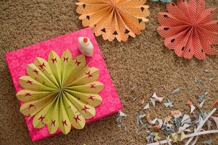 comment décorer un emballage cadeau avec un éventail en papier perforé à motif papillon, une sorte de fleur decorative en papier