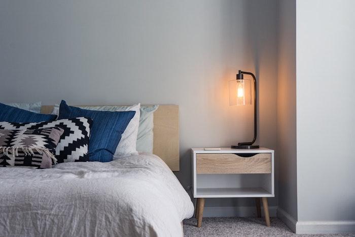 Simplicité et confort dans une chambre à coucher scandinave style, lampe sur la table de chevet retro en bois