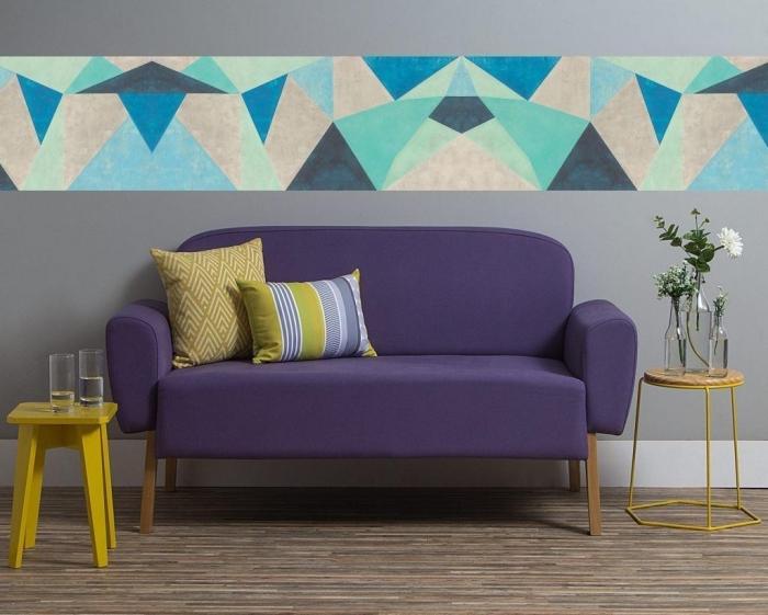 un lé unique de papier peint à motifs géométriques qui fait office de frise murale horizontale et ajoute du peps sur les murs gris