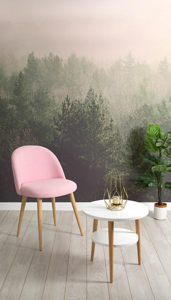 fauteuil en couleur rose poudré aux pieds en bois clair, murs revêtus de papier peint aux images paysages forets, chambre rose et gris, table deux niveaux petit et grand, deux plans blancs, parquette en beige clair