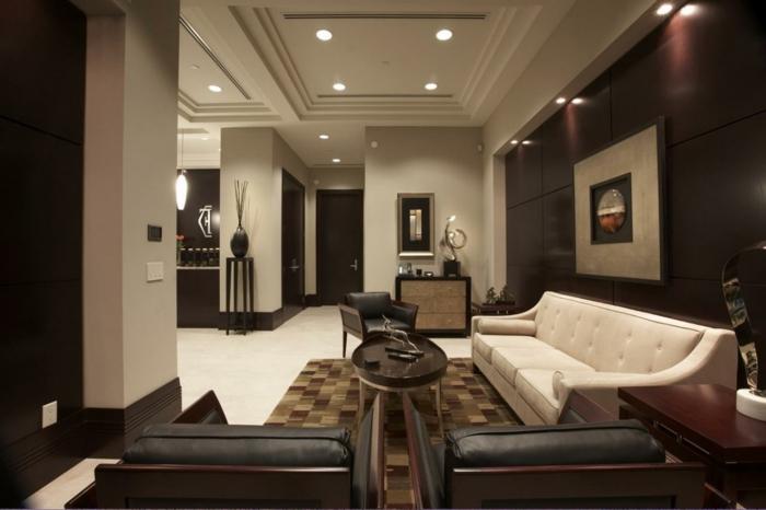 mur wengé couleur, fauteuils couleur sombre, grand canapé classique couleur crème, tapis patchwork