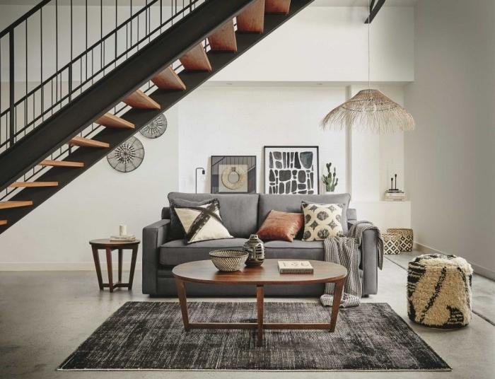 modèle d'escalier moderne de style industriel en bois et fer noir mate, accents tribaux dans un salon moderne